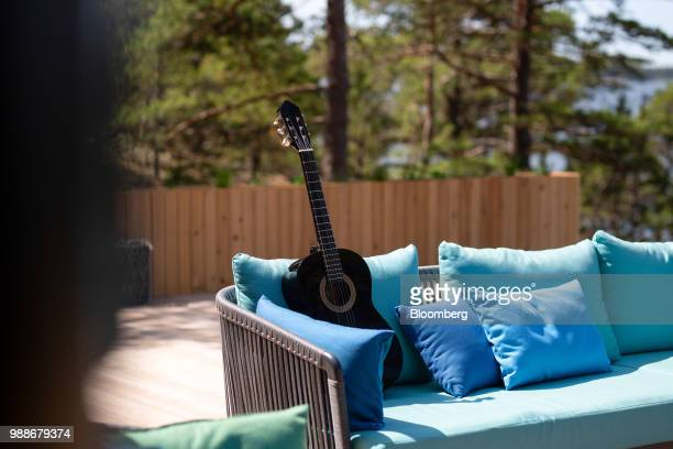 An acoustic guitar sits on an outdoor sofa on a terrace on SuperShe island near Raasepori, Finland, on Wednesday, June 27, 2018. The price of...