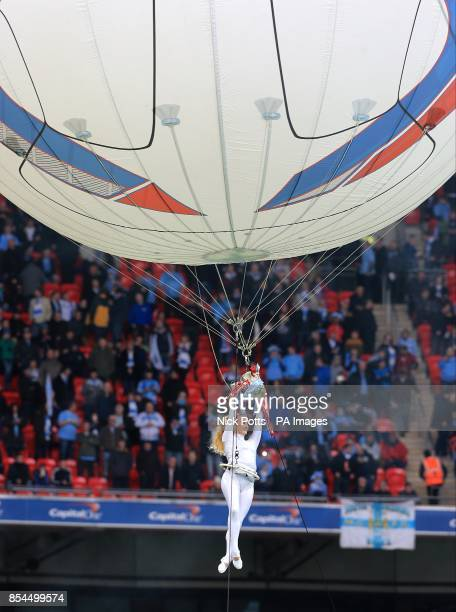 An acrobat carries the Capital One Cup Trophy through the air prior to kick off
