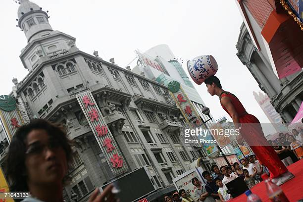 An acrobat performs to promote a department store August 13 2006 in downtown Tianjin Municipality a megacity neighboring Beijing China The State...