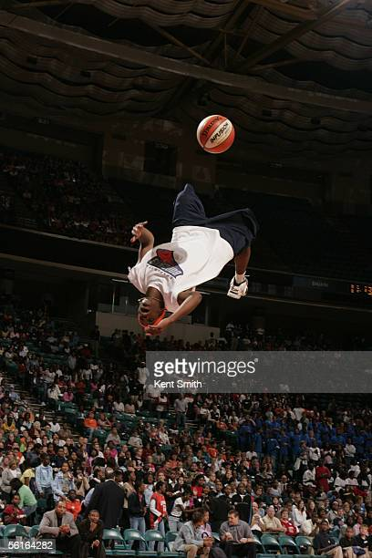 An acrobat seems to defy gravity as he attempts a trick shot during an intermission in the preseason game between the Charlotte Bobcats and the...
