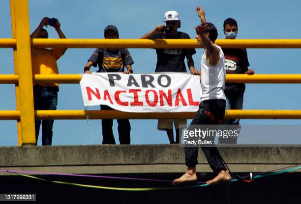 """An acrobat walks on a wire next to a sign that reads """"National strike"""" during a protest against Ivan Duque's administration on May 12, 2021 in..."""