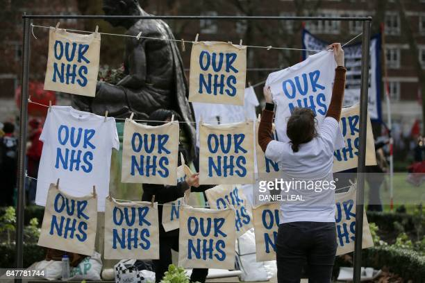 An acticvist pegs up 'Our NHS' signs and TShirts during a rally against private companies' involvement in the National Health Service and social care...