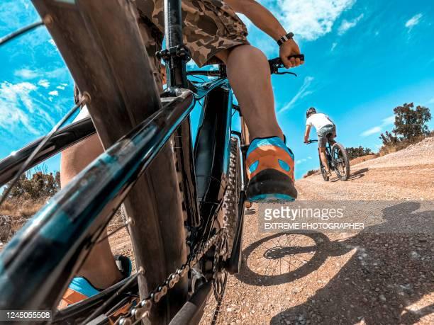 un punto d'azione di una cycler in sella a una e-bike in una gara attraverso la campagna in una giornata di sole - evento ciclistico foto e immagini stock