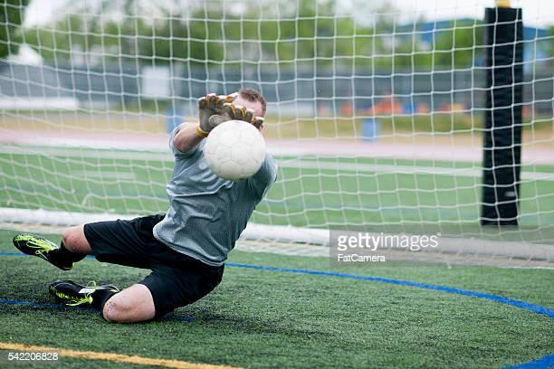 An action shot of goalie catching a soccer ball mid