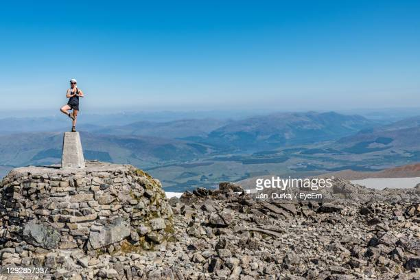 an active female model in the tree yoga pose on the top of the ben nevis peak, fort william - relaxation exercise stock pictures, royalty-free photos & images