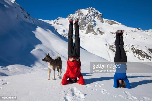 An active man and woman execute head stands below Joffre Peak.