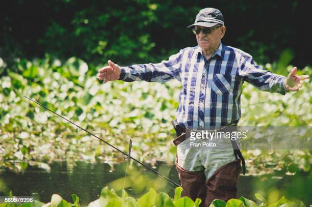 an active senior man fishing. - baldwin brothers stock pictures, royalty-free photos & images