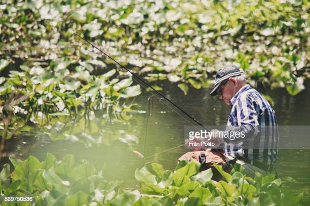 an active senior man putting bait on his fishing rod. - baldwin brothers stock pictures, royalty-free photos & images