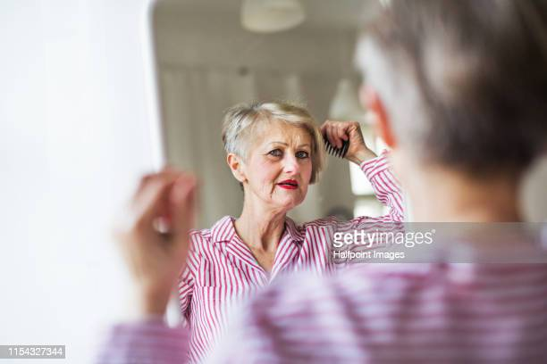 an active senior woman combing hair indoors, looking in the mirror. - penteando imagens e fotografias de stock