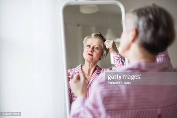 an active senior woman combing hair indoors, looking in the mirror. - look back at early colour photography stock pictures, royalty-free photos & images