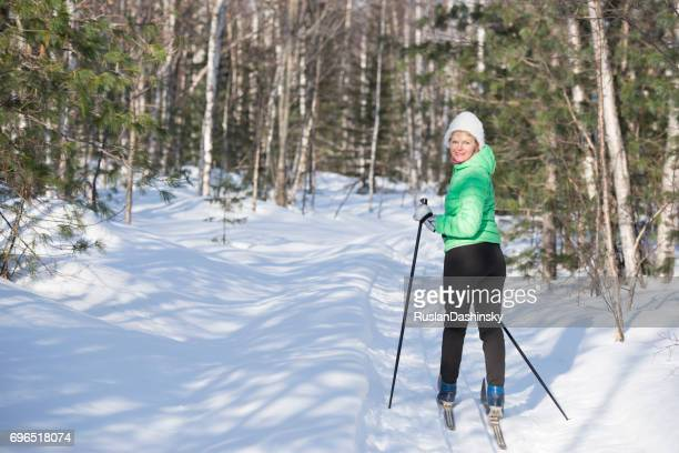 An active senior woman on cross-country ski winter vacation in a forest.
