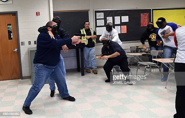 An active shooter is grabbed as he enters a classroom as students take cover during ALICE training at the Harry S Truman High School in Levittown...