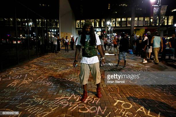 An activist adds to a growing memorial of names written on the sidewalk outside the Omni Hotel as residents and activists march nearby amid heavy...