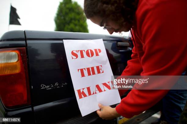 An activist affixes a protest poster against the Klu Klux Klan on his truck before driving in a caravan through the Quarryville area where the KKK...