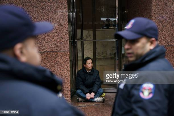 An activist blocks the doors to the building that houses the New York office of Sen Chuck Schumer during a rally for the passage of a 'clean' Dream...