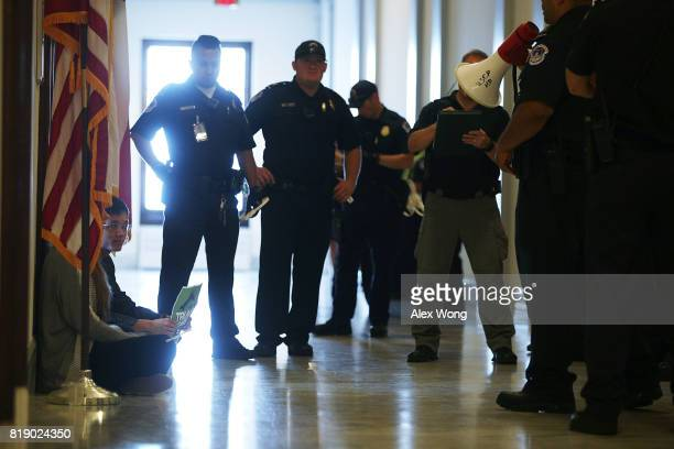 An activist blocks the doorway of U.S. Sen. Ted Cruz's office in the Russell Senate Office Building in a protest against the Republican health care...