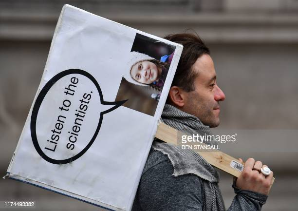 An activist carries a placard with an image of Greta Thunberg as he protests on Whitehall by Downing Street during the second day of climate change...