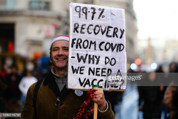 An activist carrying a placard opposing covid-19 vaccinations marches along Regent Street during a demonstration against coronavirus lockdowns in...