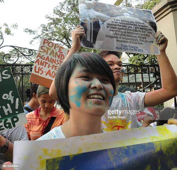 An activist covered in colored powder sings in front of the University of Santo Tomas as activists celebrate the forthcoming visit of Pope Francis to...