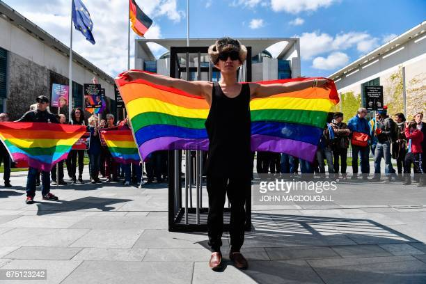 An activist displays a rainbow flag in front of the Chancellery in Berlin on April 30 during a demonstration calling on Russian President to put an...