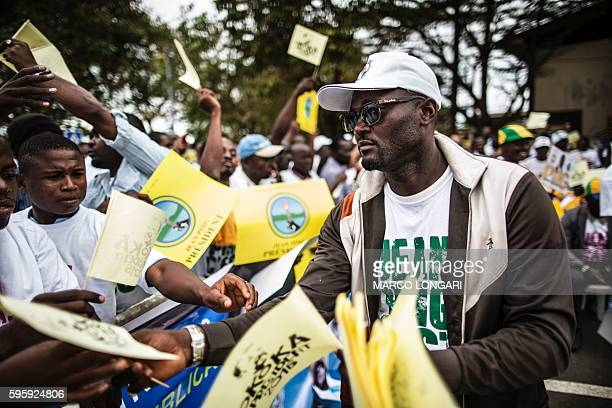 An activist distributes flags to supporters of the opposition candidate Jean Ping at a rally in Libreville on the last day of the presidential...