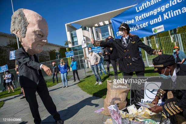 An activist dressed as an airline speaks with activist dressed as Finance Minister Olaf Scholz duringta protest outside the Chancellery against the...