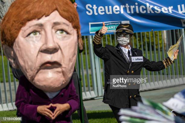 An activist dressed as an airline stewardess and an activists dressed as German Chancellor Angela Merkel taking part in a protest outside the...