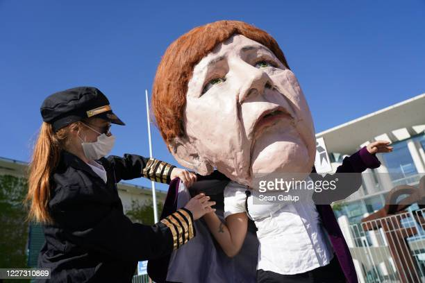 An activist dressed as an airline stewardess helps a colleague dressed as German Chancellor Angela Merkel before taking part in a protest outside the...