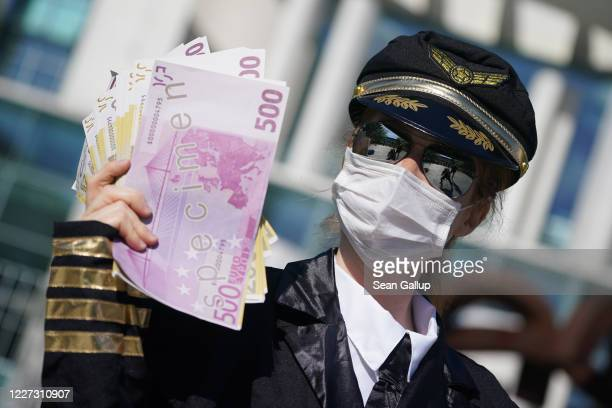 An activist dressed as an airline stewardess holds up oversized fake versions of Euro currency at a protest outside the Chancellery against the...