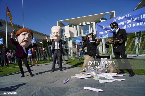 An activist dressed as German Chancellor Angela Merkel throws a paper airplane as another dressed as Finance Minister Olaf Scholz looks on during a...