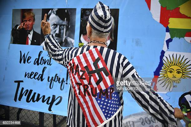 An activist dressed in a uniform used by Jewish people in concentration camps during Nazi Germany gives the finger during a protest agaisnt US...