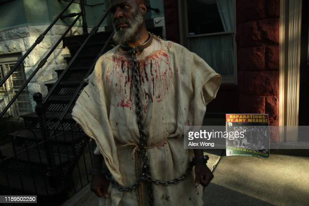 An activist dresses as a slave during a protest to mark the National Reparations Day outside the residence of U.S. Senate Majority Leader Sen. Mitch...