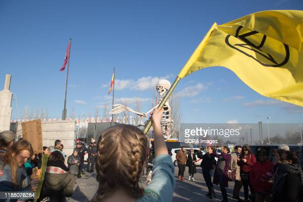 An activist flies a flag of the Extinction Rebellion group during the demonstration. There was a spontaneous saucepan protest at the entrance of...