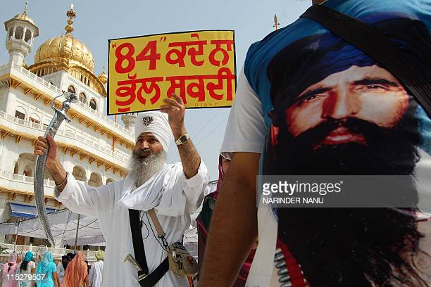 An activist from a radical Sikh prganisation wears a shirt depicting Sikh leader Sant Jarnail Singh Bhindranwale whilst another holds a placard and a...