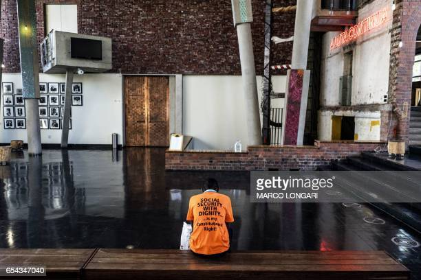 TOPSHOT An activist from Black Sash a South African human rights NGO waits in the hall at the Constitutional Court on March 17 in Johannesburg as he...