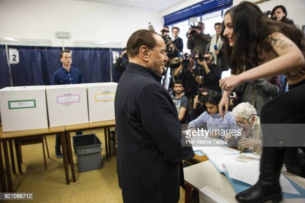 An activist from Femen confronts Leader of Forza Italia party Silvio Berlusconi as he votes at a polling station on March 4, 2018 in Milan, Italy....