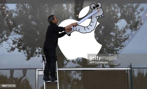 An activist from the Association for the Taxation of financial Transactions and Citizen's Action sticks a poster on the window of the Apple store...