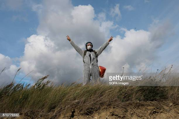 An activist from the collective Ende Gelande seen raising his arms on the mine site during a demonstration ahead of COP23 As COP 23 is about to...