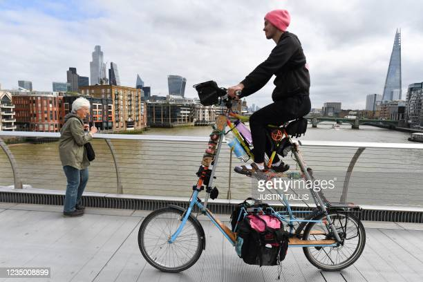 An activist from the Extinction Rebellion group cycles ove the Millennium bridge in central London on September 2, 2021 during the group's...