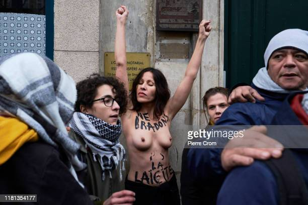 An activist from the feminist group Femen protests for a secular society as an estimated of ten thousand French citizens march from Gare du Nord to...
