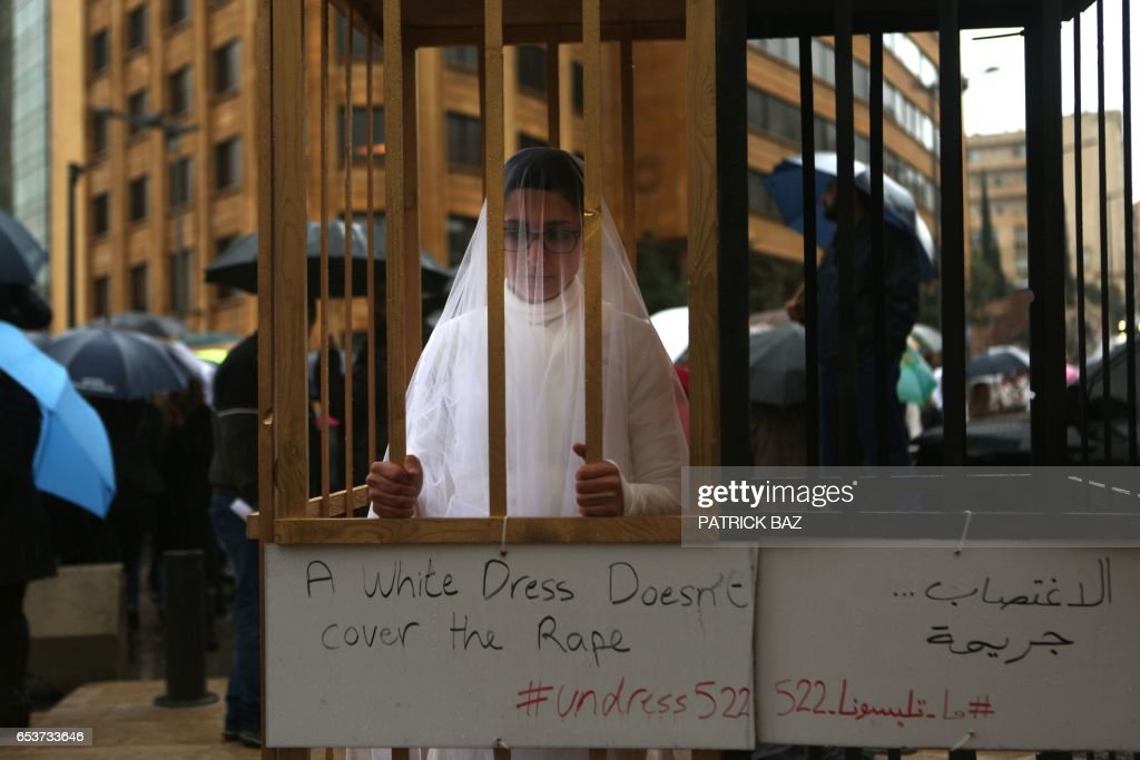 An activist from the Lebanese NGO Abaad (Dimensions), a resource centre for gender equality, dressed as a bride and wearing bandages stands in a golden cage during a protest near the parliament in downtown Beirut on March 15, 2017, as MPs are debating a vote against article 522 in the Lebanese penal code. The article shields rapists from prosecution on the condition that they marry their victim, a phenomenon that is still practised in the country, especially among conservative families whose chief aim is to preserve the family's so-called 'honour. /