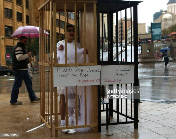 An activist from the Lebanese NGO Abaad a resource centre for gender equality dressed as a bride and wearing bandages stands in a golden cage during...