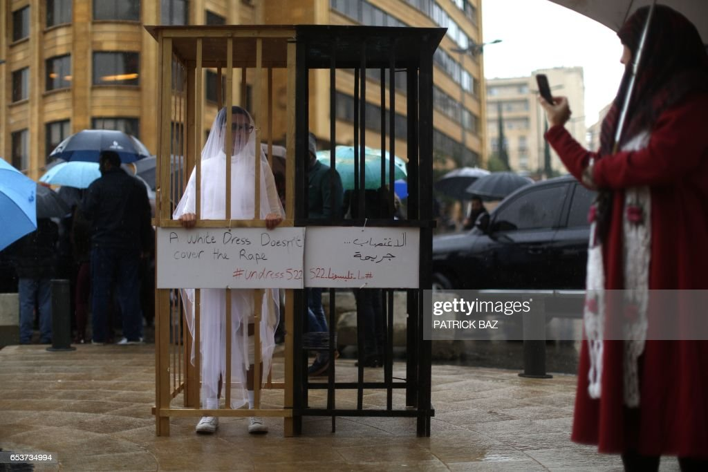 TOPSHOT - An activist from the Lebanese NGO Abaad (Dimensions), a resource centre for gender equality, dressed as a bride and wearing bandages stands in a golden cage during a protest near the parliament in downtown Beirut on March 15, 2017, as MPs are debating a vote against article 522 in the Lebanese penal code. The article shields rapists from prosecution on the condition that they marry their victim, a phenomenon that is still practised in the country, especially among conservative families whose chief aim is to preserve the family's so-called 'honour. /