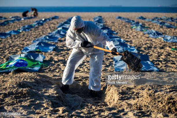"""An activist from the NGO """"Rio de Paz"""" digs a mock grave during an event to pay homage to the 400,000 dead of coronavirus and protest against official..."""