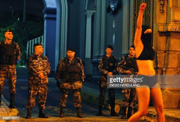 TOPSHOT An activist gestures in front of military police during a march to mourn the death of activist Marielle Franco in Rio de Janeiro on April 14...