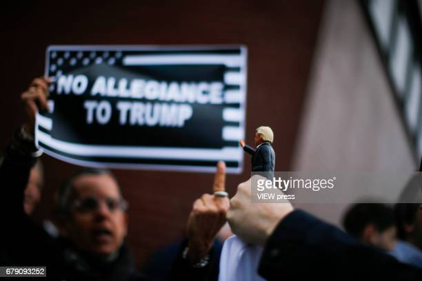 An activist gives a middle finger to a toy of US president Donald Trump as she takes part in a protest near the USS Intrepid where US president is...