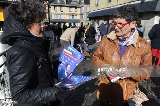 An activist gives leaflets of the French presidential election candidate for the leftwing French Socialist party Benoit Hamon on April 1 2017 in the...