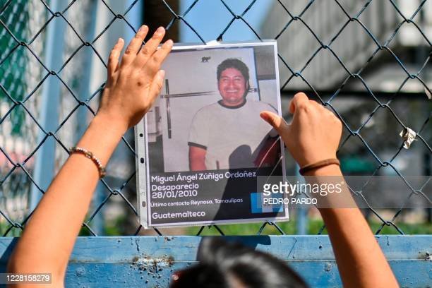 "An activist hangs a picture of a missing man after lifting an ""anti-monument"" to mark the 10th anniversary of the San Fernando Massacre in which 72..."