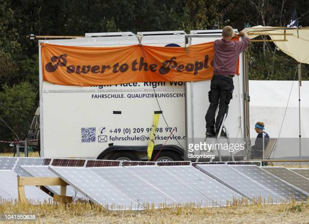 An activist hangs a 'Power to the People' banner to a kiosk behind solar panels at the Klimacamp environmental camp near the town of Immerath Germany...