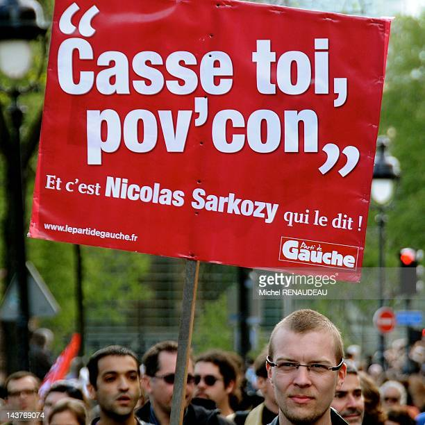 An activist hold signs saying 'Go out asshole' during annual protest march celebrating May Day on May 1 2012 in Paris France